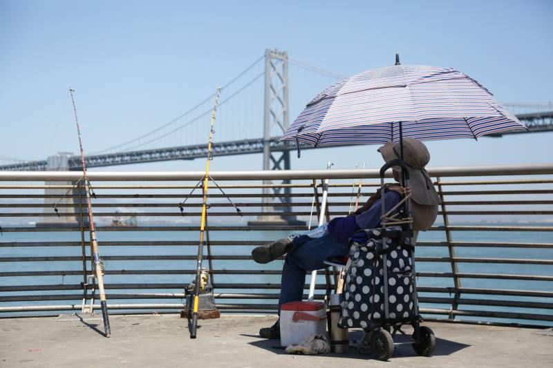 A fisherman waits under the shade of his umbrella during a heat wave.