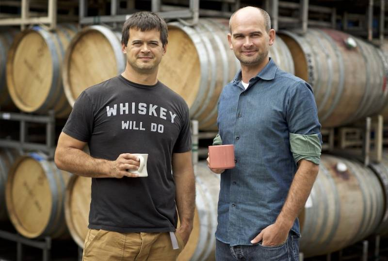 Ryan Harms and Eric Harms stand in front of big oak wine barrels.