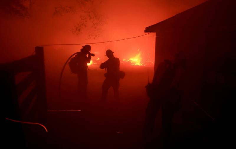 United States Forest Service firefighters from the Los Padres National Forest turn away from wind driven embers and smoke as they protect a structure from the Dixie fire.