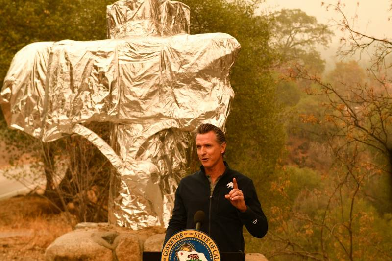 Governor Gavin Newsom speaks at a podium in a cloud of wildfire smoke.