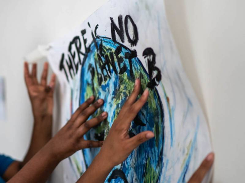 """The hands of several children hold up a handmade sign with a painting of Earth and copy that reads """"There's No Planet B."""""""