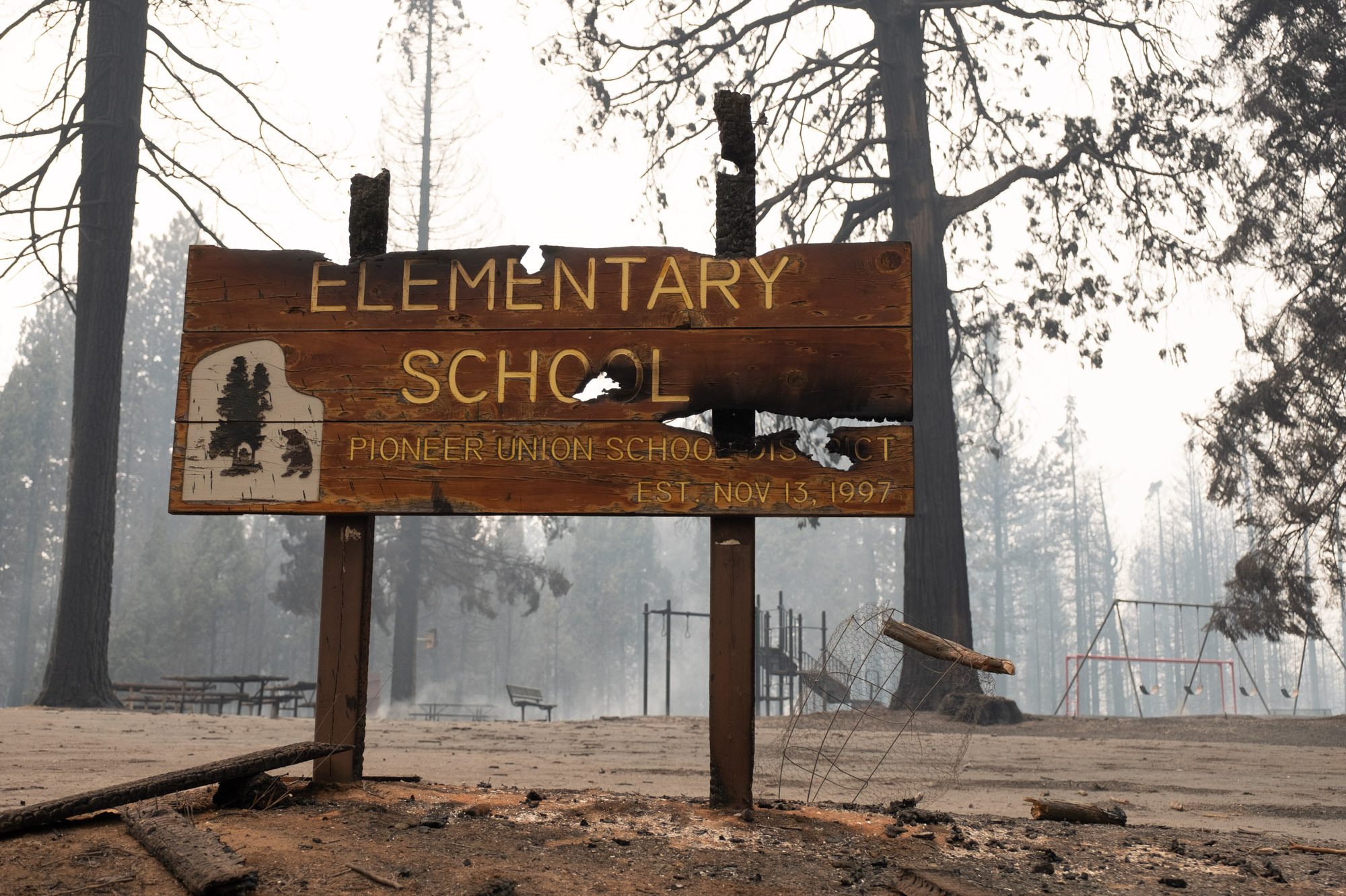 A burned entrance sign at Walter Tyler Elementary school with charred playground equipment in the background.