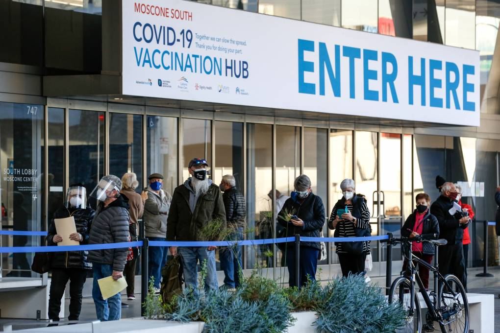 People stand in line at the mass vaccination site at San Francisco's Moscone Convention Center. It opened for healthcare workers and people over 65 on February 5, 2021 in San Francisco, California.