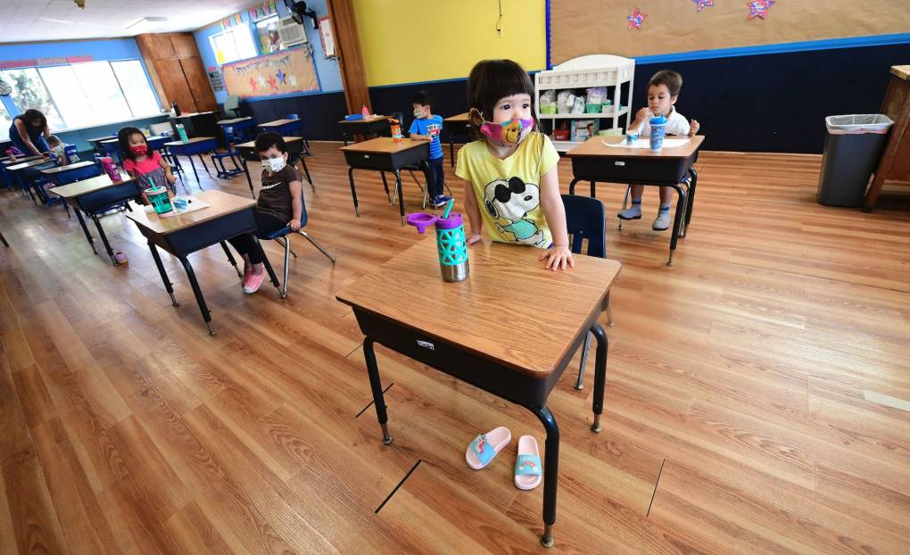 Children in a preschool class wear masks and sit at desks spaced apart as per coronavirus guidelines during summer school sessions in Monterey Park, California, on July 9, 2020. Frederic J. Brown/AFP via Getty Images