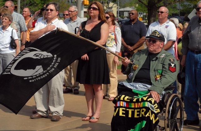 Vietnam War veteran Michael Sullivan Sr. waves a Prisoner of War/Missing in Action flag during the Vietnam veterans ceremony in Huntsville, AL.