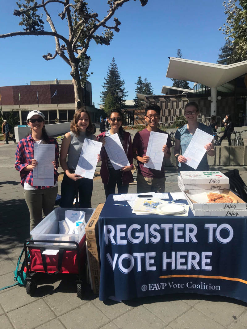 students holding up voter registration forms