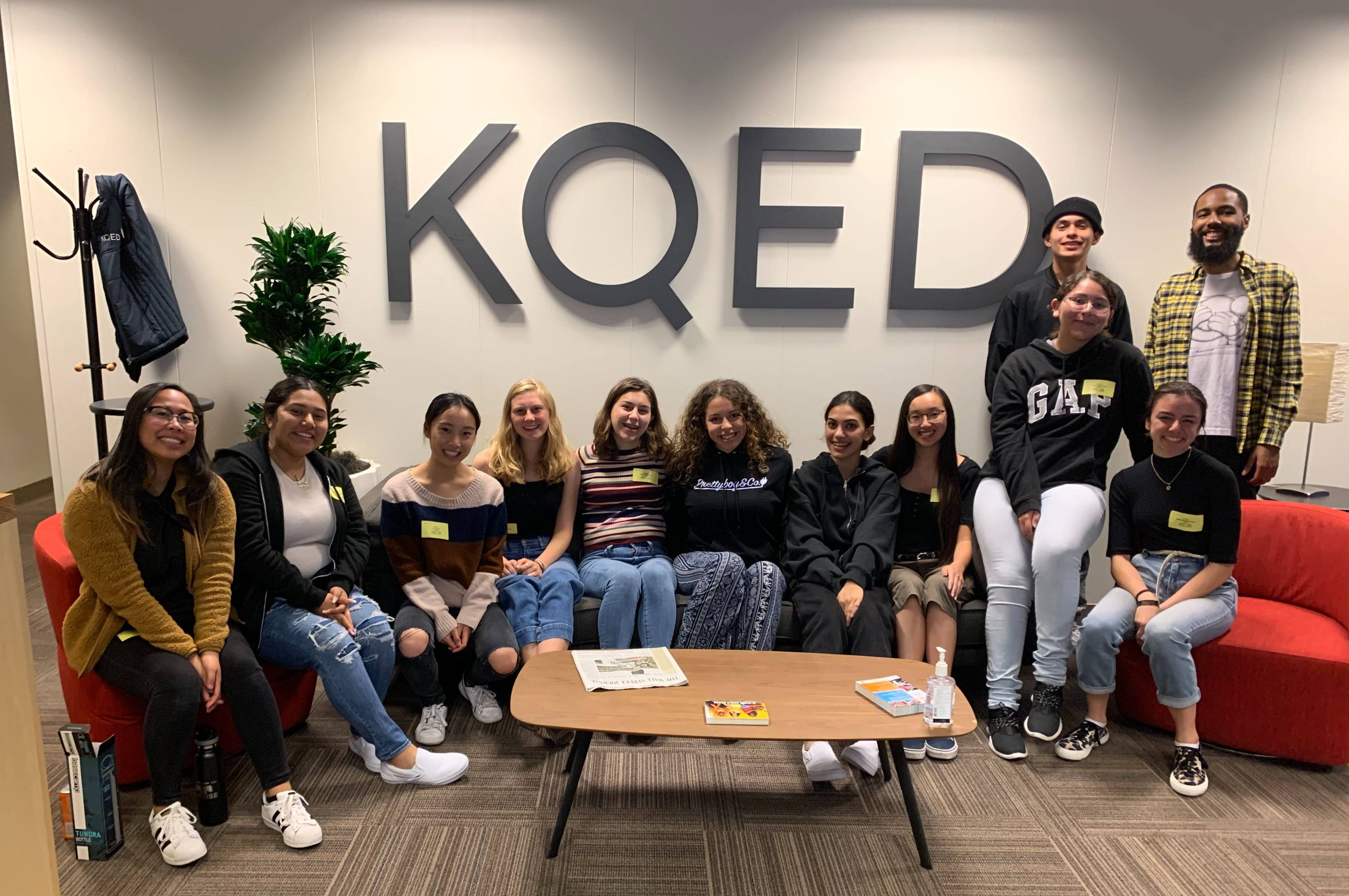 A group of about 10 teens sit on a couch in front the KQED logo in large letters. Myles Bess, host of Above the Noise, stands next to them.