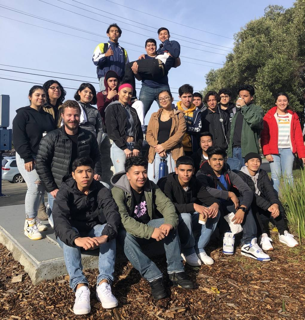 A group of about 20 students from Richmond High School pose for a photo at an outdoor location. Some are seated while some are standing.