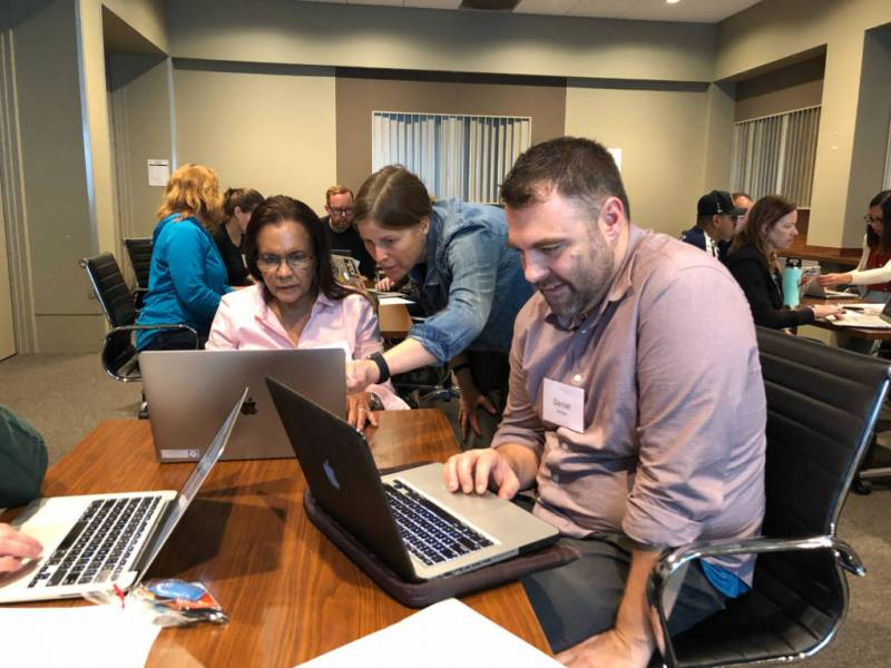 Two educators sit at a table with laptops. KQED staffer stands in the middle, pointing at one of their screens.