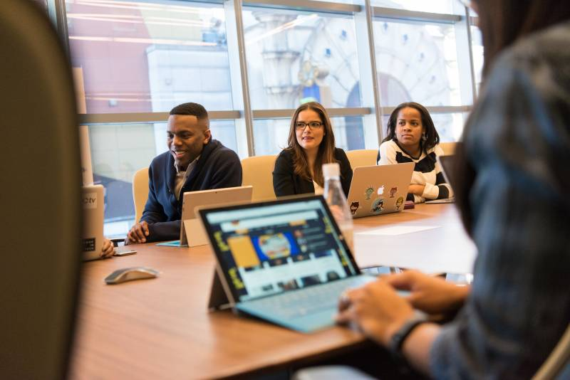 Smiling men and women sitting around a conference room table with laptops