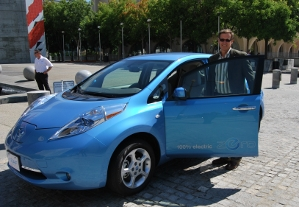 Mark Perry from Nissan standing next to the Leaf, an all electric-vehicle.