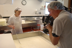 Cameraman Blake McHugh films artisan cheesemaker Maureen Cunnie in the early stages of making the Red Hawk washed rind cheese.