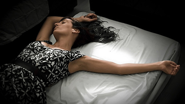 photograph of woman laying in bed.
