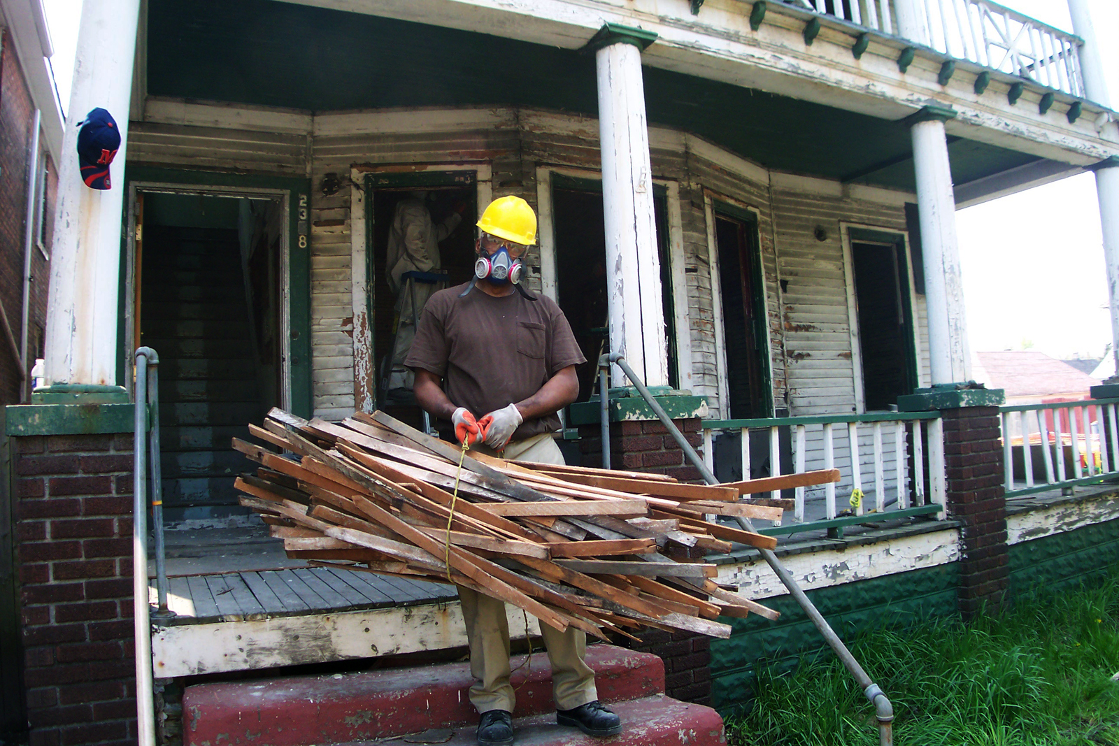 A worker from Reclaim Detroit salvages wood from a vacant home.  Image Courtesy of Reclaim Detroit.