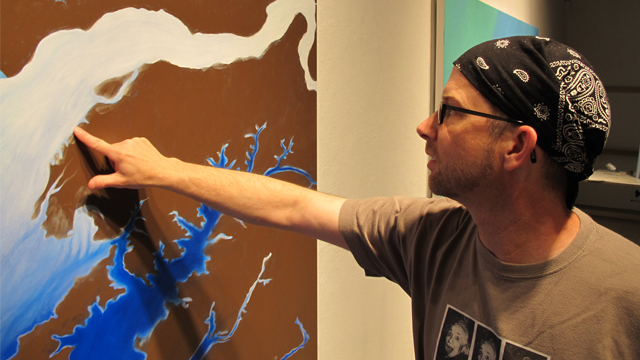 Artist John Sabraw checks the paint on one of his works in progress. The brown pigment is sourced from coal mine runoff.