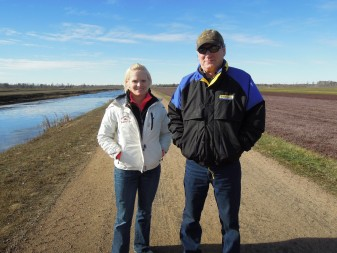 Cranberry Creek Cranberries' plant health manager Nicole Hanson and owner Bill Hatch stand between a water reservoir and a freshly harvest cranberry bed near Necedah. Photo Credit: Maureen McCollum/WPR