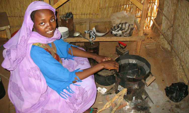 A young woman in Darfur prepares a fire with the Berkeley-Darfur Stove. Courtesy Potential Energy.
