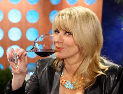 Host Leslie Sbrocco tasting wine.