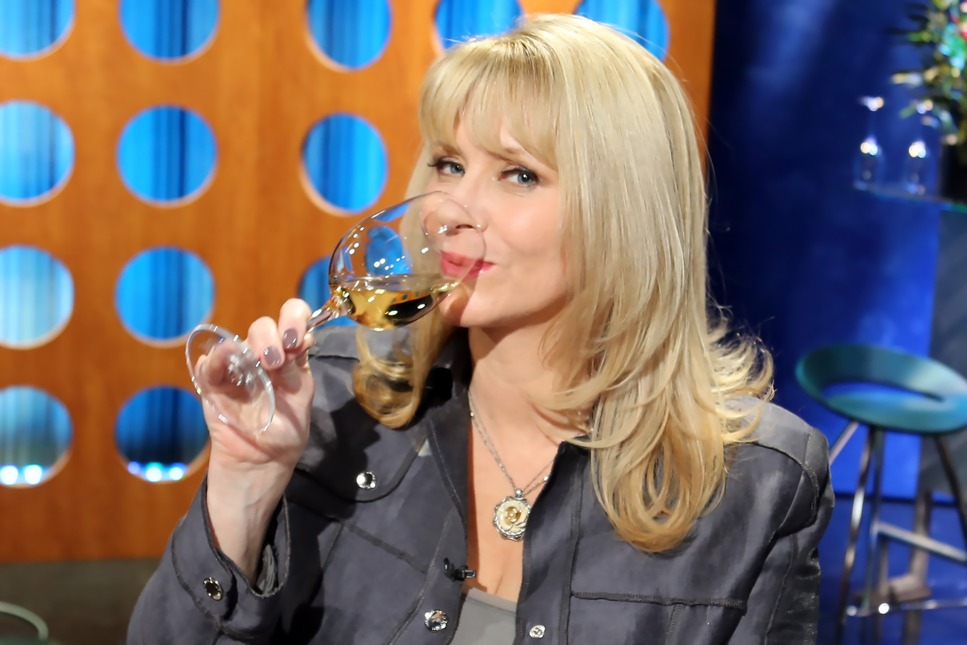 Host Leslie Sbrocco sipping wine on set
