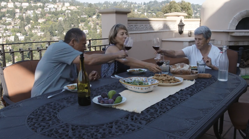 Rosetta Costantino, her husband, and her mother cheers to another bountiful meal from the garden.