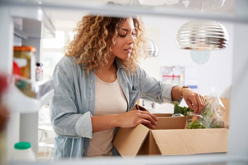 Woman pulling out groceries from a box.