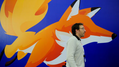 A man walks past a poster of Mozilla Firefox in 2013.