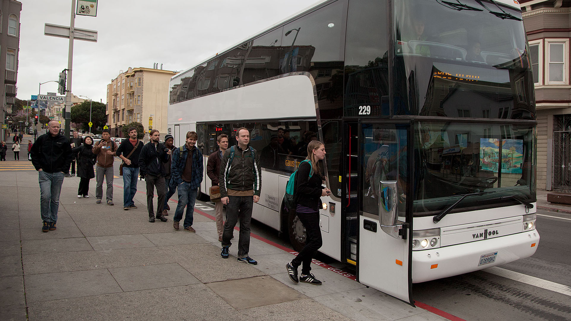 workers line up to board a bus