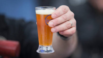a hand holding a beer glass