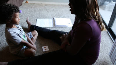 A mother and son during an in-home session of applied behavioral analysis therapy.