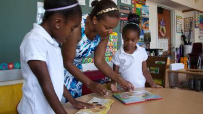 Kristin Smith (center) reads with her two daughters, six-year-old Juliana Smith (left) and four-year-old Gabriella Smith (right) in the kindergarden classroom at Sankofa Academy in Oakland, California.