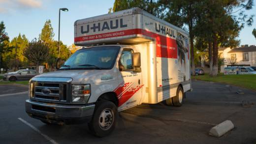 a u-haul truck is parked in the parking lot of an apartment building in the San Francisco Bay Area.