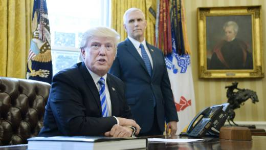 President Donald Trump reacts with Vice President Mike Pence (R) after Republicans abruptly pulled their health care bill from the House floor, in the Oval Office of the White House on March 24, 2017 in Washington, DC