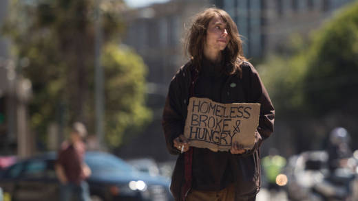 A homeless man begs on a center divider in San Francisco, California on June, 27, 2016.