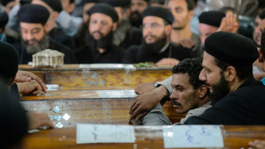 Relatives of killed Coptic Christians grieve by the coffins during the funeral at Abu Garnous Cathedral in the north Minya town of Maghagha, on May 26, 2017.