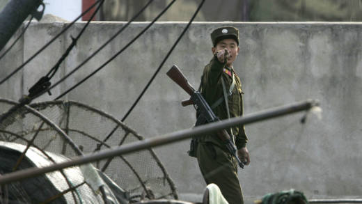 A North Korean soldier reacts to be photographed on the banks of the Yalu River in the North Korean town of Sinuiju, opposite the Chinese border city of Dandong October 21, 2006 in Sinuiju, Democratic People's Republic of Korea.