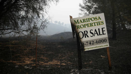 half burned real estate sign stands on the side of the road during the Detwiler Fire on July 19, 2017 in Mariposa, California.