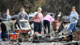 Residents search for an engagement ring at a burned residence in Santa Rosa, California on October 20, 2017. Residents are being allowed to return to their burned homes on October 20 to grieve and search through remains. Around 5,700 homes and businesses have been destroyed by the fires, the deadliest in California's history.