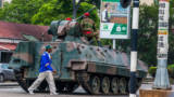A man walks past an armored personnel carrier that's stationed by an intersection as Zimbabwean soldiers regulate traffic in Harare on November 15, 2017.