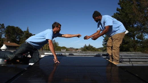 SolarCraft workers Craig Powell (L) and Edwin Neal install solar panels on the roof of a home on February 26, 2015 in San Rafael, California.