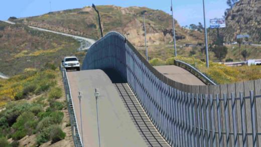 A border patrol car drives past a border fence.