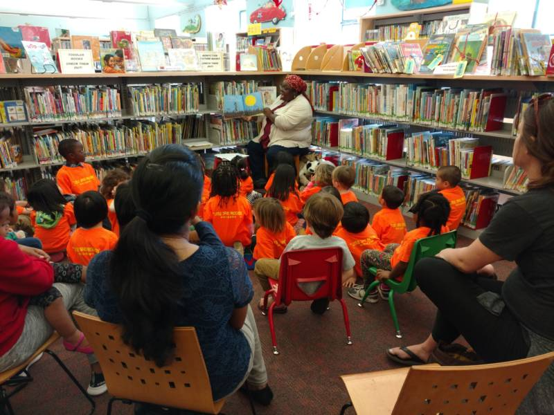 Children's librarian Mahasin Abuwi Aleem reads to children during story time at Oakland's Main Library.