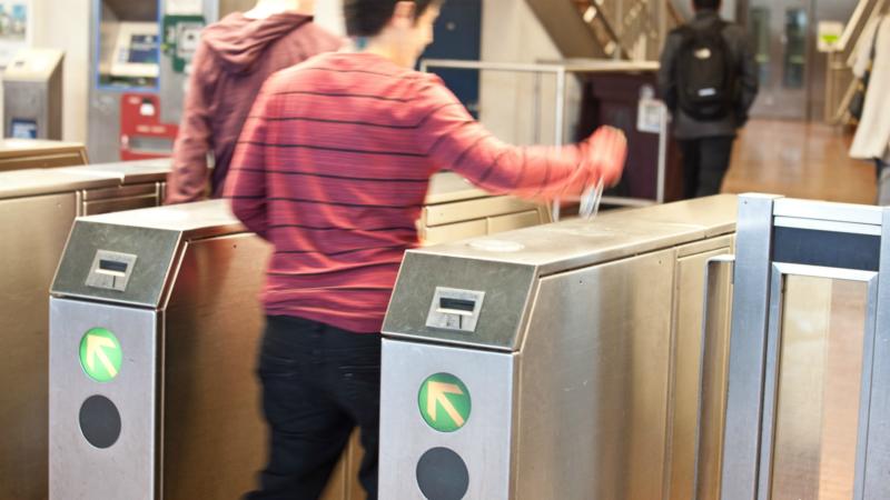 Person walking through a BART fare gate.