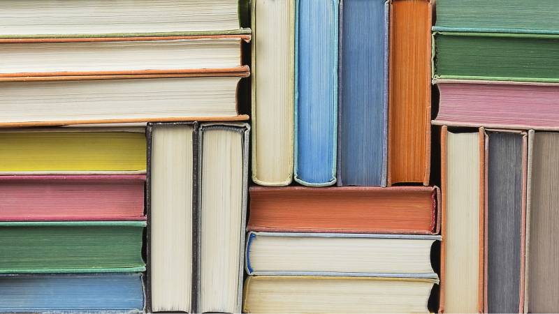 colored books, stacked asymmetrically, with their pages facing the camera