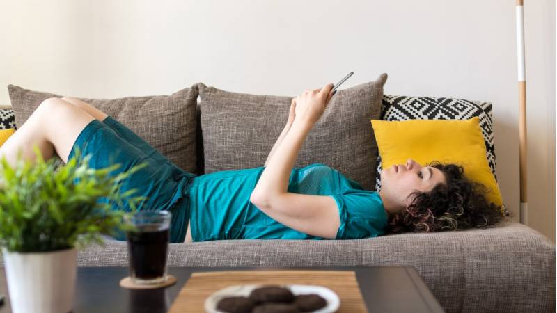Side view shot of a young woman using digital tablet while lying down on a sofa at home with green plant, beverage and cookies on the table in front of her