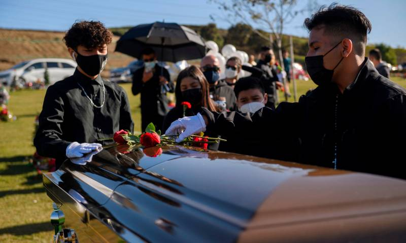 Youth gather around the coffin and place roses on top of it.