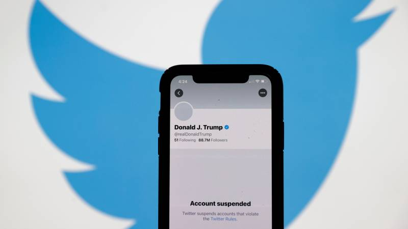 Phone screen with Donald Trump's suspended twitter account stands in front of Twitter backdrop.