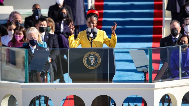 Young black woman wearing a yellow coat and red hat stands at podium with arms raised.