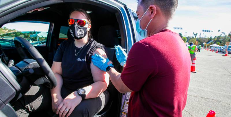 USC Doctor administers vaccine to patient who sitting in their car