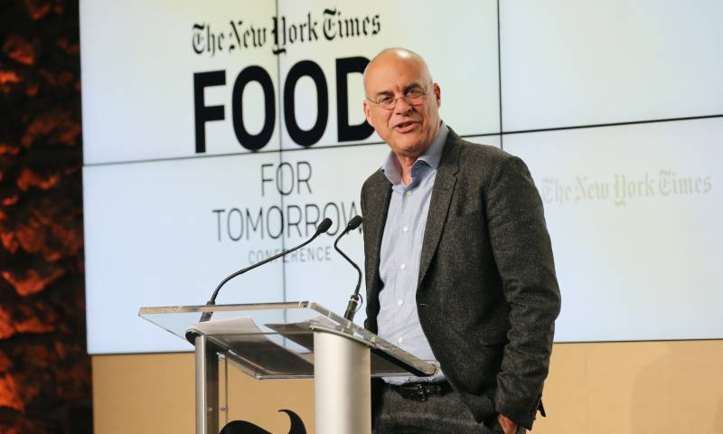 Mark Bittman stands at the podium addressing the audience at the New York Times Food for Tomorrow Conference