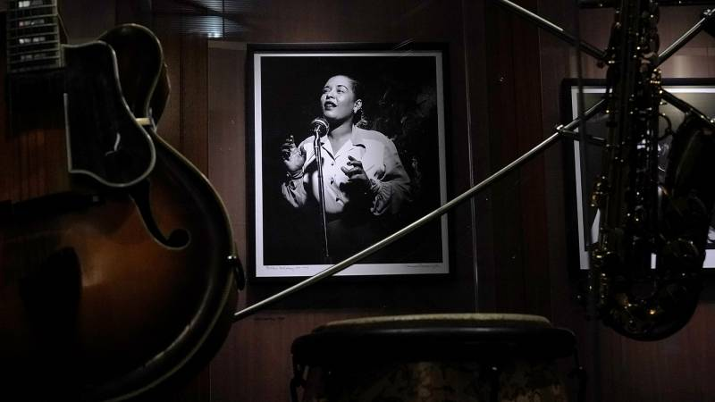 A portrait of Billie Holiday hanging on the wall surrounded by instruments